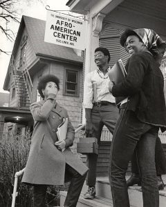 "African American students stand on the front steps of a building under a sign that reads ""The University of Wisconsin Afro-American Center, 935 Univ. Ave."""