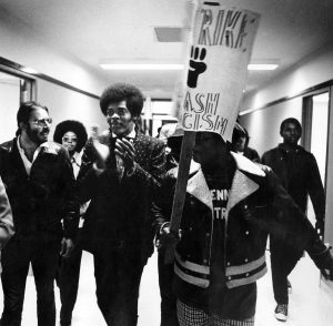 Kwame Salter walks through Van Hise Hall with others, one holding a protest sign.