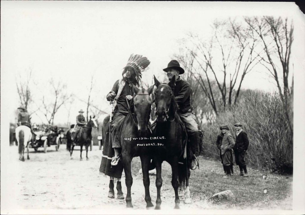 Two men dressed for the 1916 UW Circus. Both on horseback, one dressed as a Native American man in redface makeup, and another dressed as a United States calvary officer.