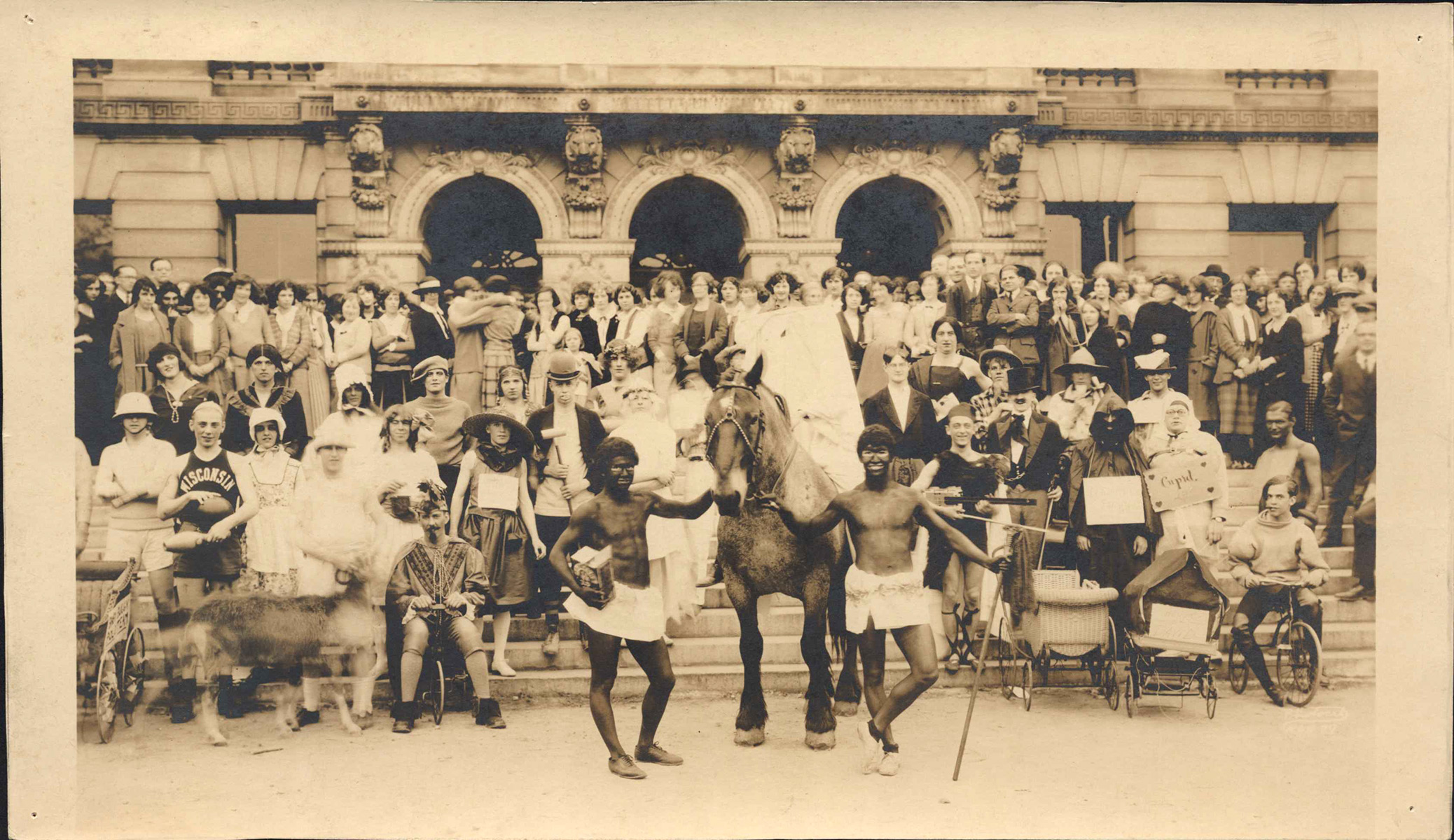 Large group photo of Haresfoot Club initiation in 1923. Depicts many students in various costumes including blackface.