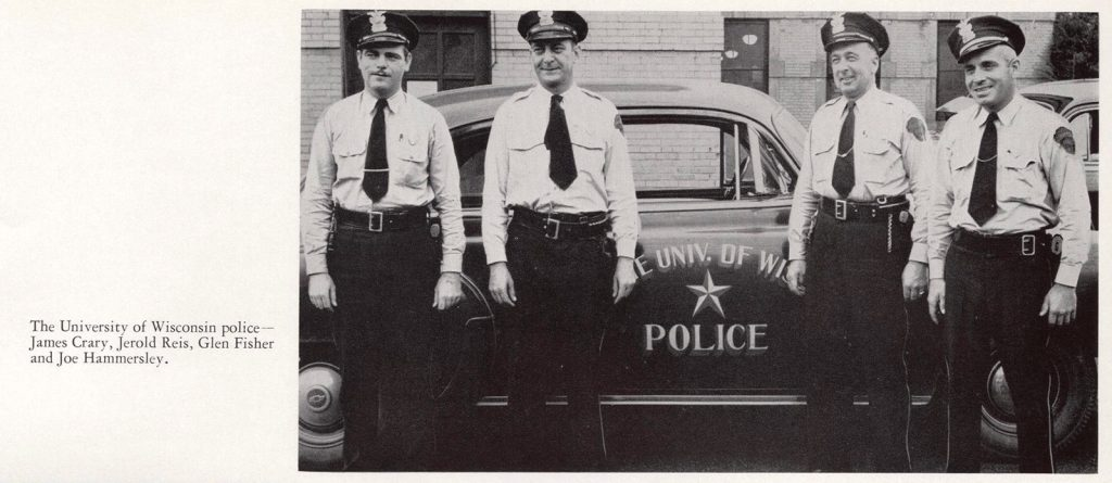 Four University of Wisconsin police officers – James Crary, Jerold Reis, Glen Fisher, and Joe Hammersley – stand in front of a UW–Madison police car.