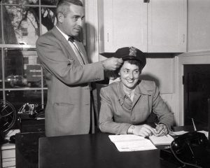 The first police woman Genevieve Dohse works at her desk while a Mr. Joe Hammersley fixes her police officer's hat. October 22, 1951.