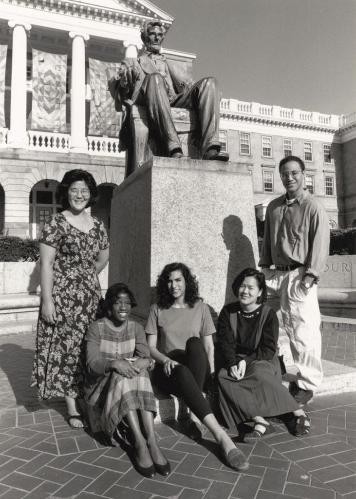 A black and white photo depicts five Chancellor's Scholars posing in front of the Abraham Lincoln statue on Bascom Hill.
