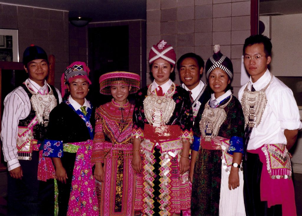 Seven Hmong American students pose for a picture wearing traditional Laotian clothing at the Union Theater in Memorial Union.
