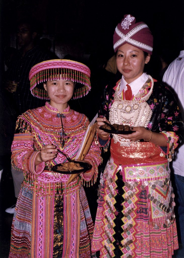 Two students, dressed in traditional Laotian clothing, from the Hmong American Student Association stand and eat at 1999 Multicultural Orientation and Reception (MCOR) at Memorial Union.