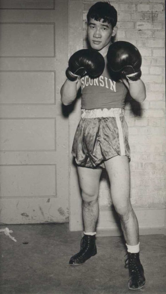Black and white photo of Akio Konoshima in his boxing uniform with gloves and fists raised.